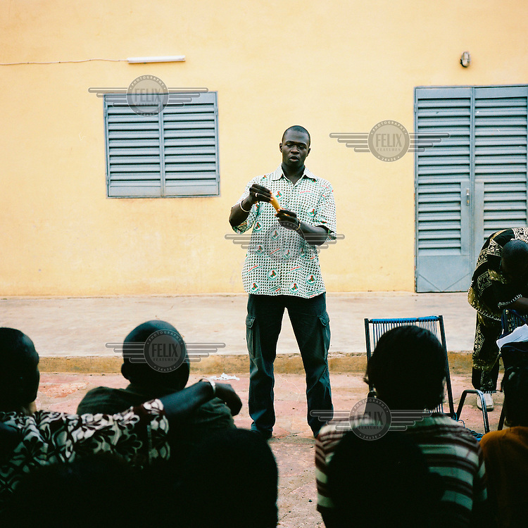 An educator from the Centre for Treatment, Activities and Counselling for People living with HIV/AIDS (CESAC), which is the main organisation working with AIDS patients in Mali, explain how to use a condom to teenagers in Bamako.