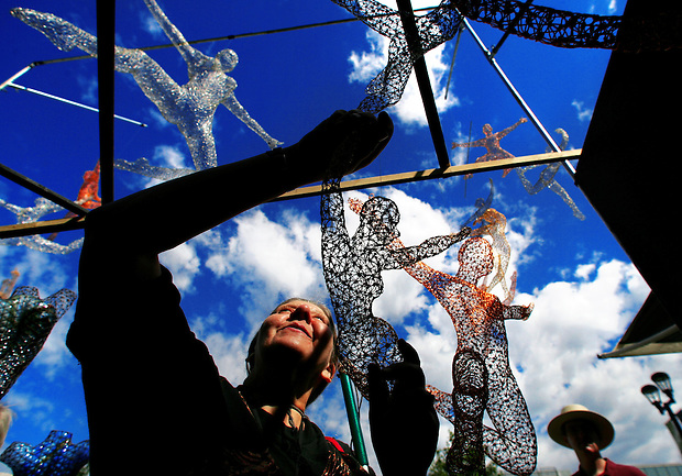 "Cynthia Qloud of Des Moines feels the woven wire sculptures of San Francisco artist Michael Gard Saturday morning at the Des Moines Arts Festival.  Qloud, who is blind, loves to visit the festival, as many artists will allow her to touch their work.  ""You don't get to do that at a museum,"" she says."