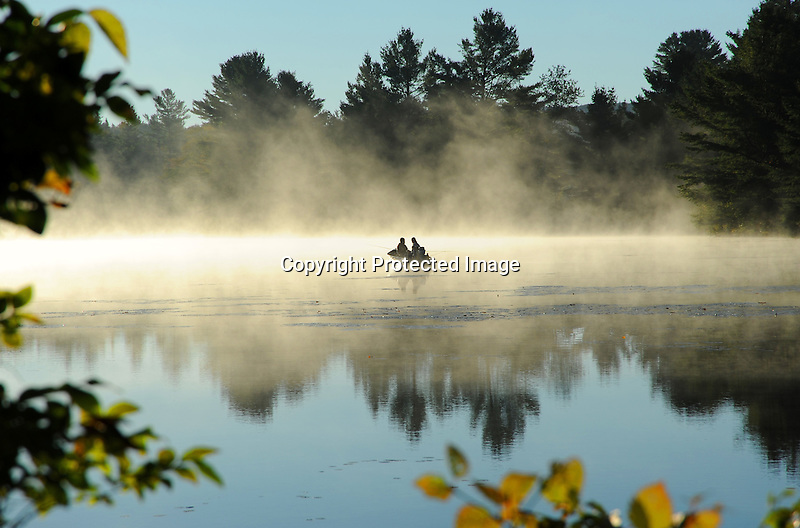 Couple Enjoying Fishing from their Boat on an Early Misty Morning in New Hampshire USA