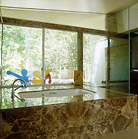 The bath is encased in marble and the picture window affords views of the garden