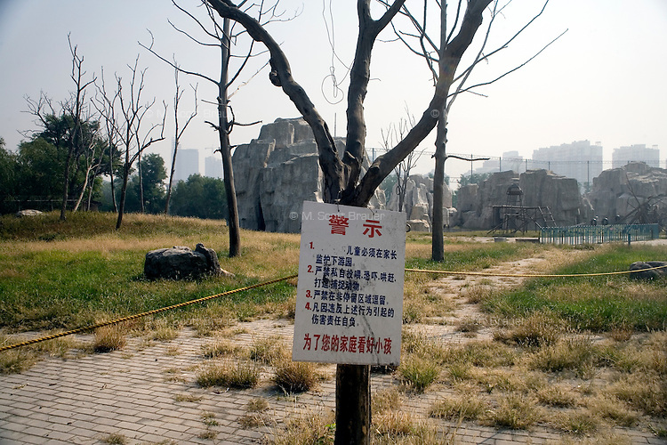Leafless trees stand in a barren field that serves as the habitat for a group of macaque monkeys in the Tianjin Zoo in Tianjin, China.  A sign hanging on a tree instructs visitors not to feed the animals and to keep control of their children.