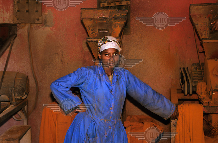 A female labourer poses for a photograph at the 'Berbere' herb mill in Medeber Market.