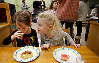 NWA Media/DAVID GOTTSCHALK - 12/19/14 - Larke McQuade, left, and Bobbie Lebens (cq) enjoy cookies in the classroom of Jamie VanHorn and Amy Davis during the Winter Solstice Celebration at Walnut Farm Montessori School in Bentonville Friday December 20, 2014. The school held a celebration inviting friends and family to enjoy cookies, cider, hot chocolate and listen to songs and poems by the students and faculty in the Natural Playground.