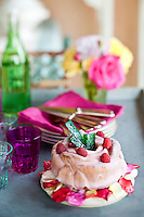 A cake with pink frosting decorated with fresh raspberries and candied rose petals is placed on a table with matching napkins and glasses