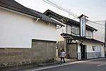 A walks her dog past Nakayu Sake Brewery in Kami Town, Miyagi Prefecture,  Japan on 02 Sept. 2012. Photographer: Robert Gilhooly