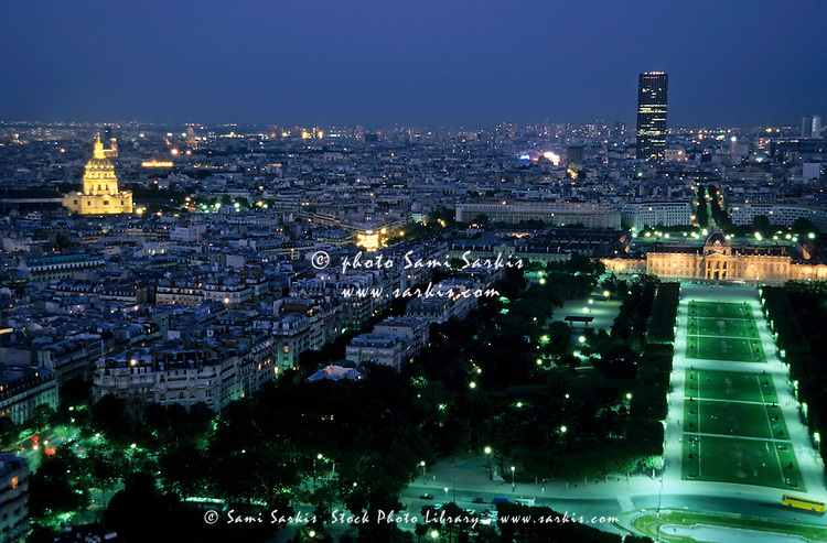 City buildings as seen from the Eiffel Tower at night including the Montparnasse Tower, Les Invalides, Champ de Mars and École Militaire, Paris, France.