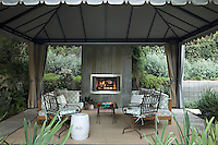 The large draped pavilion makes a comfortable and cosy outdoor room even on a chilly evening as it has an open fire