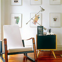 A corner of the living room is furnished with a mid-century chair and side table