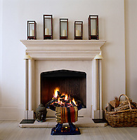 Rosewood lanterns are lined up along the mantelpiece with a blue porcelain footstool in front of the fireplace