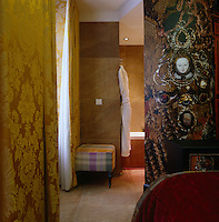 Golden yellow damask curtains, decoupage wallpaper and the stone tiled walls create a textured effect in this bathroom