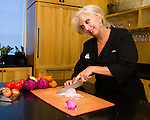 An award winning composite image of professional chef Sue Shattuck dicing an onion while two nearby onions react as they await a similar fate.