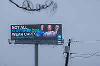 """A billboard showing healthcare workers and reading """"Not all superheroes wear capes #allinthistogether"""" is seen in Medford, Massachusetts, on Mon., April 27, 2020 during the ongoing Coronavirus (COVID-19) global pandemic. Companies have modified most advertising to reflect the uncertainty of life during the pandemic and to show support for frontline workers, especially healthcare workers."""