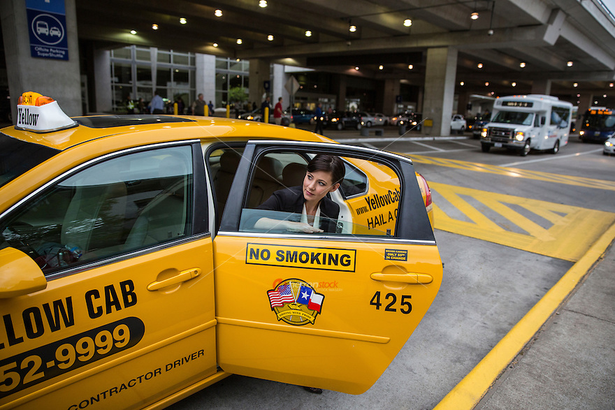 Attractive business woman exits taxi cab at the Austin–Bergstrom International Airport (ABIA).