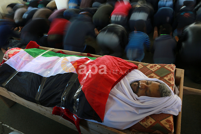 Palestinian mourners pray next to the body of 48-year-old Yussef al-Buhairi draped in the Palestinian flag during his funeral at a mosque in the al-Maghazi refugee camp, located in in the centre of the Gaza Strip, on December 28, 2015. Buhairi who was wounded at the Gaza border during clashes with the Israeli army the previous week died early on December 27 from his injuries, the Gaza health ministry said. Photo by Yasser Qudih