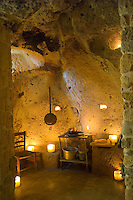 The kitchen in this folly is simply furnished and is lit by candlelight