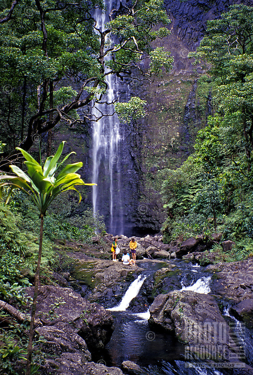 Hikers rest near Hanakapiai Falls, reached by a side trail off the Kalalau Trail on the Na Pali Coast of Kauai