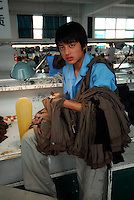 """Workers in a textile factory that produces socks in  Datang known as  """"Sock Town"""" in Zhejiang Province, China. The town in Zhejiang Province makes more than 2.5 pairs for every human alive."""