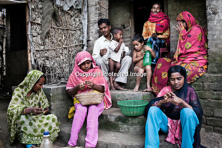 21 year old Rafik Gazi, (3rd from left) from the Chowduli class is seen with his entire family in the courtyard of their house in Chaymalpur village of North 24 Parganas in West Bengal, India. Photo: Sanjit Das/Panos for The Wall Street Journal. Slug: ICASTE