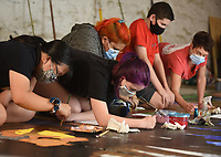 Leigh Davis (from left), a ninth grader at Farmington Junior High School, Josslyn McCall, Bianca Curciaga, Landon Gadberry, all sophomores at Farmington High School, and Gretchen Wilkes, art teacher at Farmington Junior High School, paint Thursday, July 30, 2020, on an 8 foot by 24 foot mural in the Down Under at Fenix Gallery on the downtown square in Fayetteville. Students in Wilkes' Farmington Junior High School art class partnered with local artist Octavio Logo to create the mural that will be displayed Saturday, August 22, in Farmington on the side of a building near Hwy. 62. Check out nwaonline.com/200731Daily/ and nwadg.com/photos for a photo gallery.<br /> (NWA Democrat-Gazette/David Gottschalk)