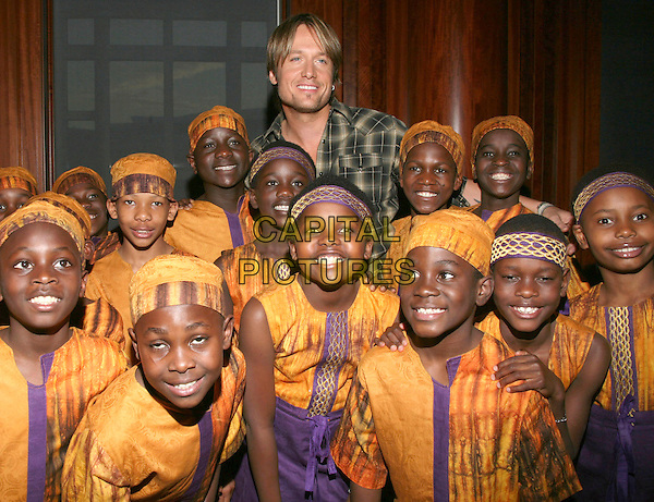 KEITH URBAN with the African Children's Choir.Nashville 4 Africa Concert held at the Schermerhorn Symphony Center, Nashville, TN, USA..April 22nd, 2009.half length grey gray green plaid shirt yellow purple traditional outfits dress kids.CAP/ADM/RR.©Randi Radcliff/AdMedia/Capital Pictures.