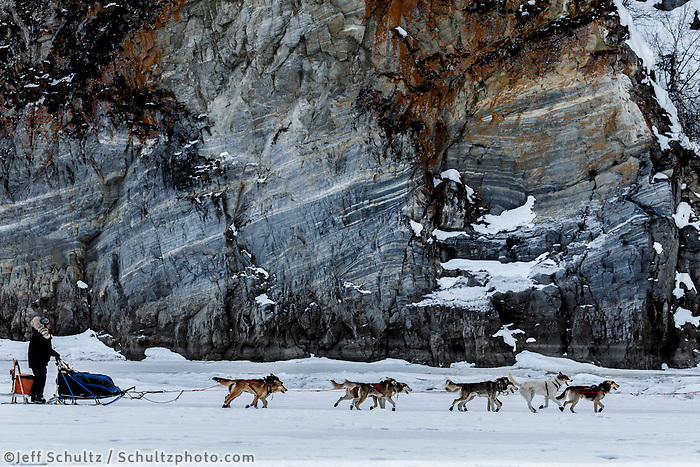 Michelle Phillips and team run along the rock cliffs shortly after leaving the Ruby Checkpoint during the 2016 Iditarod.  March 11, 2016    <br /> <br /> Photo by Jeff Schultz (C) 2016  ALL RIGHTS RESERVED