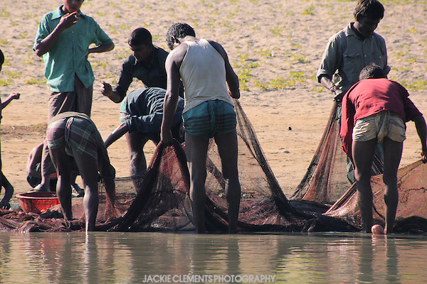 Fishermen with their traditional lungi wraps shortened and tucked into their waists inspect their nets on the banks of the Sangu River, Bandarban