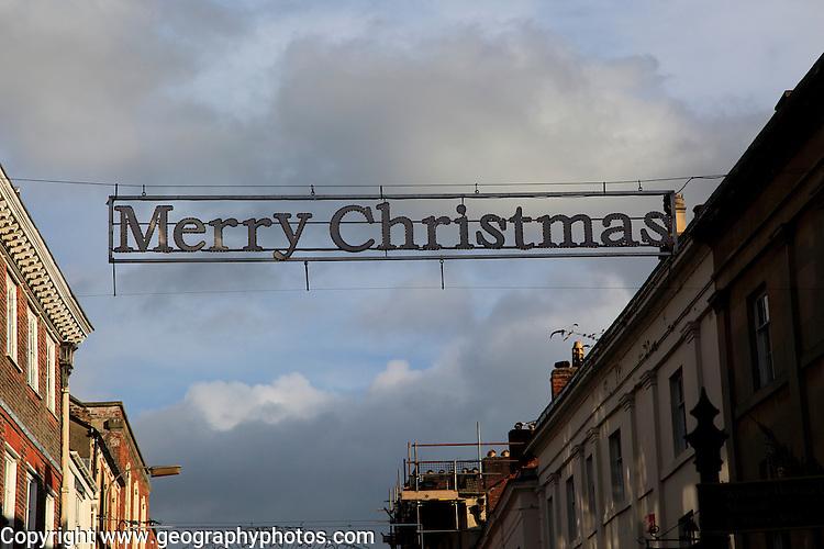 Merry Christmas banner sign between buildings, Devizes, Wiltshire, England, UK