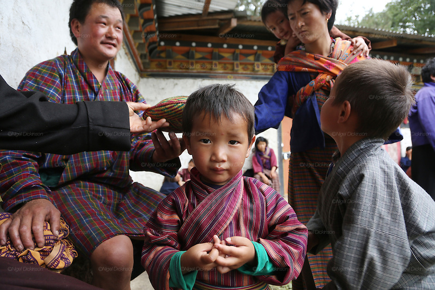 A boy making a Buddhist prayer meditation symbol with his fingers. A traditional Puja celebration, a yearly Buddhist festival by the local community, Chuchizshey temple, Bumthang, Bhutan..Bhutan the country that prides itself on the development of 'Gross National Happiness' rather than GNP. This attitude pervades education, government, proclamations by royalty and politicians alike, and in the daily life of Bhutanese people. Strong adherence and respect for a royal family and Buddhism, mean the people generally follow what they are told and taught. There are of course contradictions between the modern and tradional world more often seen in urban rather than rural contexts. Phallic images of huge penises adorn the traditional homes, surrounded by animal spirits; Gross National Penis. Slow development, and fending off the modern world, television only introduced ten years ago, the lack of intrusive tourism, as tourists need to pay a daily minimum entry of $250, ecotourism for the rich, leaves a relatively unworldly populace, but with very high literacy, good health service and payments to peasants to not kill wild animals, or misuse forest, enables sustainable development and protects the country's natural heritage. Whilst various hydro-electric schemes, cash crops including apples, pull in import revenue, and Bhutan is helped with aid from the international community. Its population is only a meagre 700,000. Indian and Nepalese workers carry out the menial road and construction work.