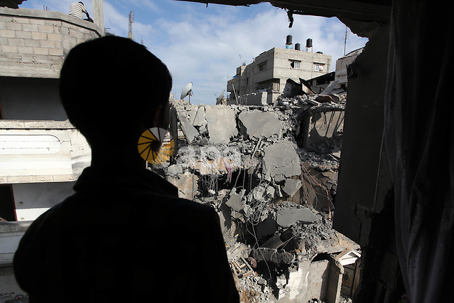 A Palestinian man looks at the remains of house, which witnesses said was hit by an Israeli air strike in Gaza city August 9, 2014. Israel launched more than 20 aerial attacks in Gaza early on Saturday and militants fired several rockets at Israel in a second day of violence since a failure to extend an Egyptian-mediated truce that halted a monthlong war earlier this week. The Israeli military said that since midnight it had attacked more than 20 sites in the coastal enclave where Hamas Islamists are dominant, without specifying the targets. Medical officials in Gaza said two Palestinians were killed when their motorcycle was bombed and the bodies of three others were found beneath the rubble of one of three bombed mosques. The air strikes which lasted through the night also bombed three houses, and fighter planes also strafed open areas, medical officials said. Photo by Ashraf Amra