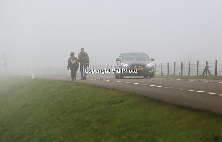 Foto: VidiPhoto<br /> <br /> DRIEL/HOMOET - Een kleine wereld woensdag in een groot deel van Nederland. Het midden, oosten en zuiden van ons land had woensdag te maken met een dichte tot zeer dichte mist, die voor veel overlast zorgde. Foto: Gevaarlijkse situaties op de Rijndijk bij het Gelderse Driel.