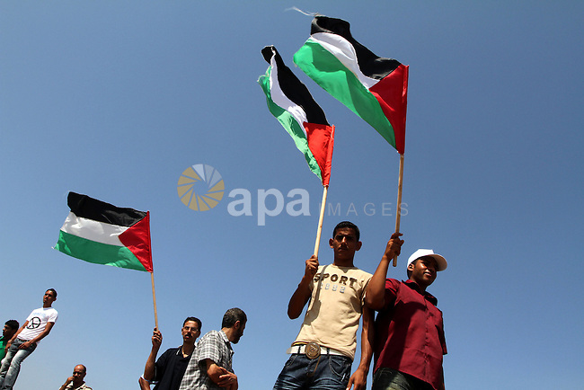 Palestinians hold Palestinian flags during a demonstration against the blockade on Gaza, near the border between Gaza and Israel outside the Maghazi refugee camp, central Gaza Strip, Sunday on Sept. 26, 2010. Israel and neighboring Egypt have kept Gaza under blockade since the militant Hamas seized power in Gaza in June 2007 . Photo by Ashraf Amra