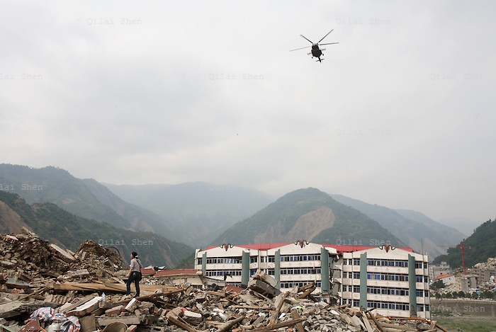 A helicopter flies over head as a resident searches for signs of trapped life on collapsed buildings in Beichuan, Sichuan, China on 15 May 2008. China now estimates the death toll to be around 50,000 as prospects of survival for those still buried diminishes.