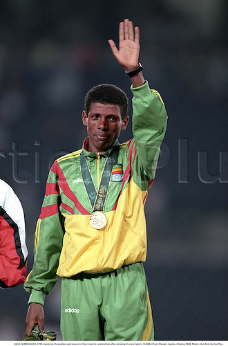 HAILE GEBRSELASSIE (ETH) stands on the podium and waves to the crowd in celebration after winning his race, Men's 10,000M Final, Olympic Games, Atlanta, 9608. Photo: Glyn Kirk/Action Plus...1996.olympics.win.winner.winners.wins.victor.victory.victories.celebrations celebration celebrates joy celebrating.athletics athlete.run runner runners running.distance.man men men's.track event.waving wave.male