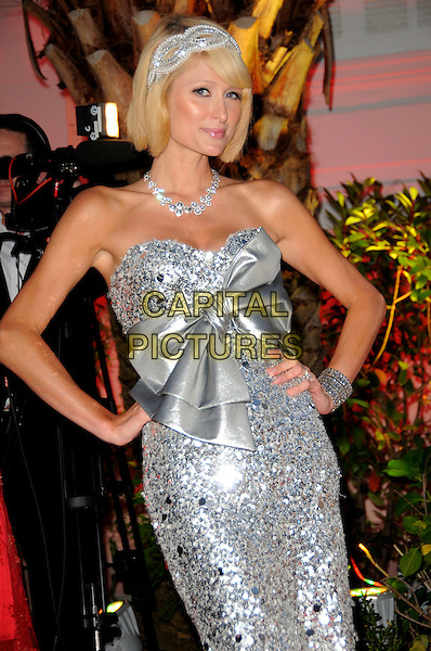 PARIS HILTON .The Akvinta Presents A Night of Hollywood Domino Party at The House at Cannes during the 62nd International Cannes Film Festival, Cannes, France..May 18th, 2009 .half length silver beads beaded dress sequins sequined ribbon bow strapless necklace diamonds hairband hair band hands on hips .CAP/CAS.©Bob Cass/Capital Pictures.