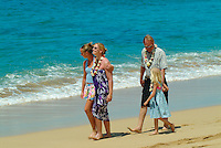 Tourist family walking on Mahaka beach, west side of Oahu