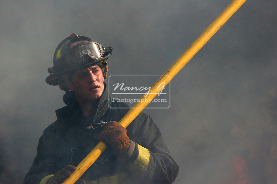 A firefighter holding a yellow pole to use on a house fire scene