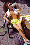 Sexy glamour photo of a young woman tennis player drinking water from a bottle lying in a lounge chair topless