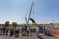 Pictured: A crane lifts the Bascule Bridge over river Tawe in the Morfa area of Swansea, south Wales. Sunday 14 July 2019<br /> Re: A 110 year old bridge has been moved for restoration in Swansea, Wales, UK.<br /> Preparation work has been under way for weeks and the Bascule Bridge near the Liberty Stadium has been lifted by a crane, in one piece.<br /> It took more than 20 workers, a 53m (174ft) crane and and a truck to complete the manoeuvre.<br /> The 70-tonne Grade II listed bridge will then be assessed and restored at Afon Engineering in Swansea Vale, and re-installed next year.<br /> The bridge was pivotal to the area's time as the world copper capital, and its hinged steel structure would lift to allow for river traffic to pass through.