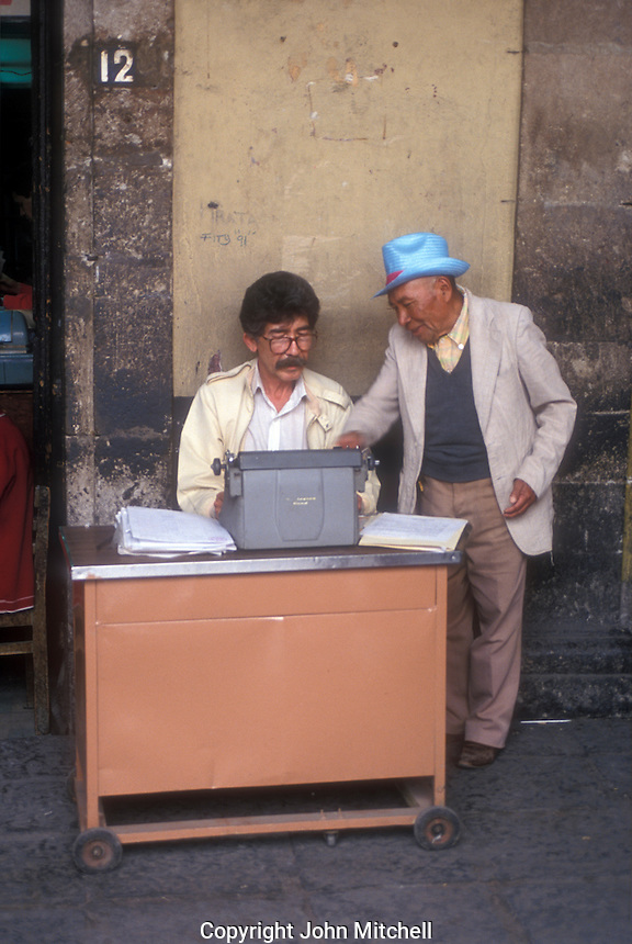 Public scribe helping a client in Plaza Santo Domingo, Mexico City