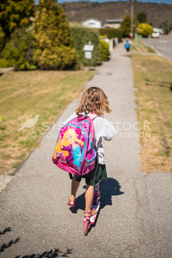 Primary school children in uniform leaving the school grounds on a summers day, New Zealand - stock photo, canvas, fine art print