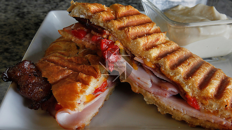 The Gourmet Panini has ham, bacon, fire-roasted red peppers, and three-pepper Colby Jack cheese on a croissant.