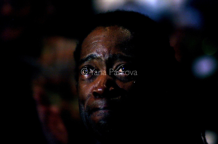 """Malik Camara, 47, teacher from Chicago, cries while watching the inauguration of Barack Obama as President of the United States in the theater of the DuSable Museum of African-American History in Chicago, Illinois, on the Presidential Inauguration Day, Tuesday, January 20, 2009.  Camara said, """"I expect Obama to stay grounded, spiritually, mentally, and physically, because a lot in his job will be overwhelming, but as long as he stays grounded, he will be okay."""" Camara's phone number: 773.239.1771 (Photo by Yana Paskova for The New York Times)..Assignment ID: 30075164A"""
