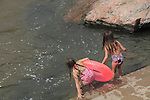 Children playing with inner tube at Boulder Creek, Boulder, Colorado .  John offers private photo tours in Denver, Boulder and throughout Colorado. Year-round.