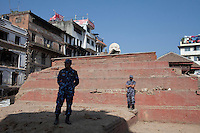 Nepali police man stands guard in front of a destroyed temple at Kathmandu Durbar Square, Kathmandu, Nepal.<br />  May 03, 2015