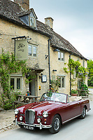British made Alvis TD21 drophead coupe Series 1 classic parked by the Maytime Inn public house in Asthall village in The Cotswolds, England