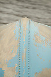 View of aluminum boat hull and rivets and blue peeling paint.