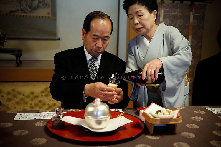 Nara, April 2011 - In a Kaiseki restaurant during a wedding, a guest is holding his glass while the waitress is pouring beer.
