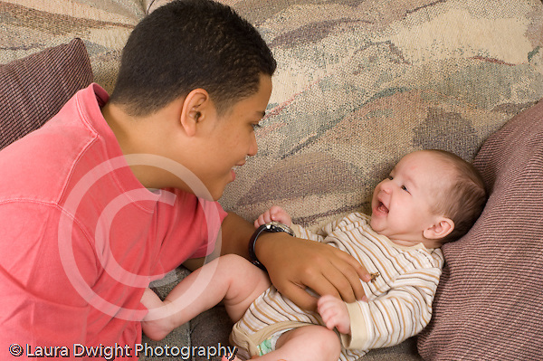 3 month old baby boy inteaction with 15 year old teenage half brother horizontal Hispanic Puerto Rican