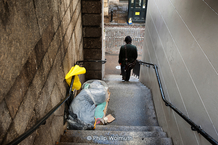 A rough sleeper on a stairway at London Bridge.