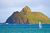 A windsurfer skims across the water in front of Moku Nui.  View from Kailua Beach.